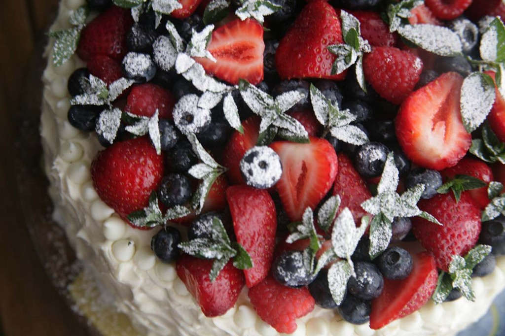 4-layer chocolate cake with white chocolate cream cheese frosting and berries